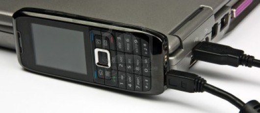 6131538-photo-concept-phone-connected-to-laptop-via-usb-cable